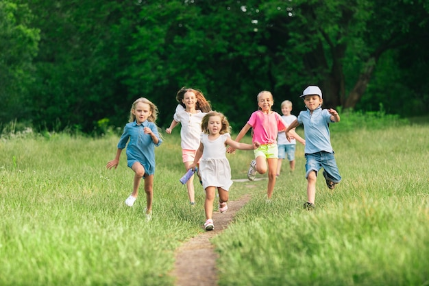 Children running on meadow with summer sunlight.