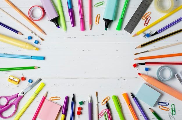 白い木製の背景に勉強、創造性、事務用品のための子供用アクセサリー。学校のコンセプトに戻る。スペースをコピーします。
