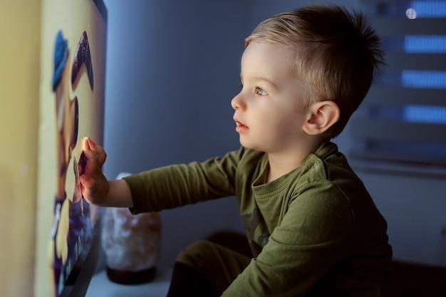 テレビや漫画への子供の中毒。その少年はテレビの画面に触れた。テレビの前に座って漫画を見つめている子供のクローズアップショット。就寝前に子供を楽しませる