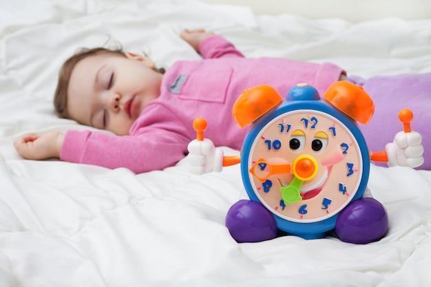眠っている子供の背景に子供の目覚まし時計。赤ちゃんの日モードのコンセプト写真