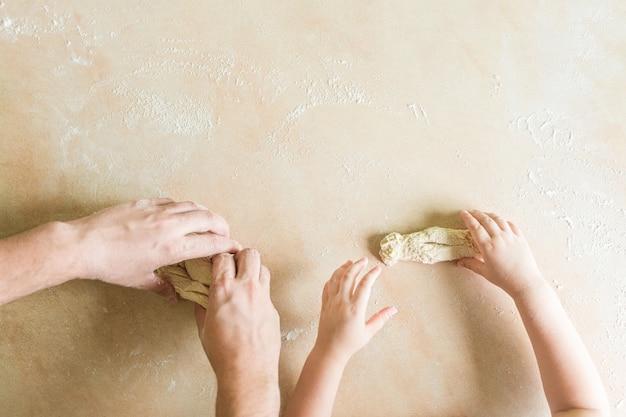 子供とお父さんの手が生の生地を作る