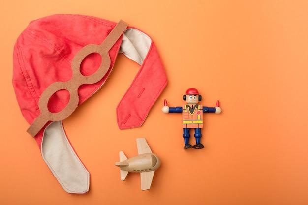 子供の背景、パイロットの帽子、おもちゃの木製飛行機と男、オレンジ色の背景、上面図