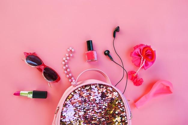 ピンクの背景に化粧品と女性のアクセサリーが付いている子供のバックパック。上面図、フラットレイ。