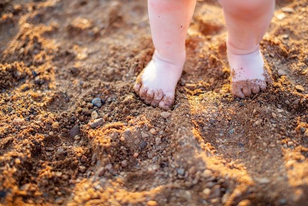 황금빛 모래 해변 클로즈업에 여름에 아이들의 맨발. 어린이 안전의 개념입니다. 아이들과 함께하는 레크리에이션의 개념.