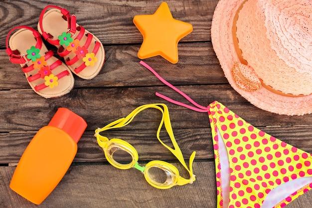 Детские пляжные аксессуары на старой деревянной поверхности. тонированное изображение. Premium Фотографии
