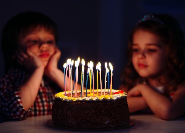 子供の誕生日。キャンドルで誕生日ケーキの近くの子供たち。