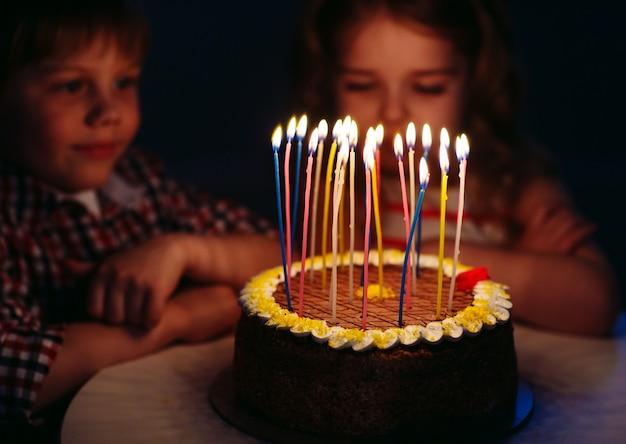 Children's birthday. children near a birthday cake with candles.