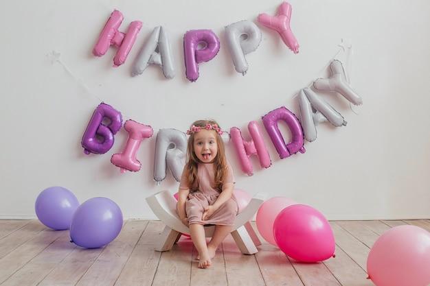 아이들의 생일. 행복 한 어린 소녀는 카메라 앞에서 포즈, 웃는 아이 혀를 보여줍니다.