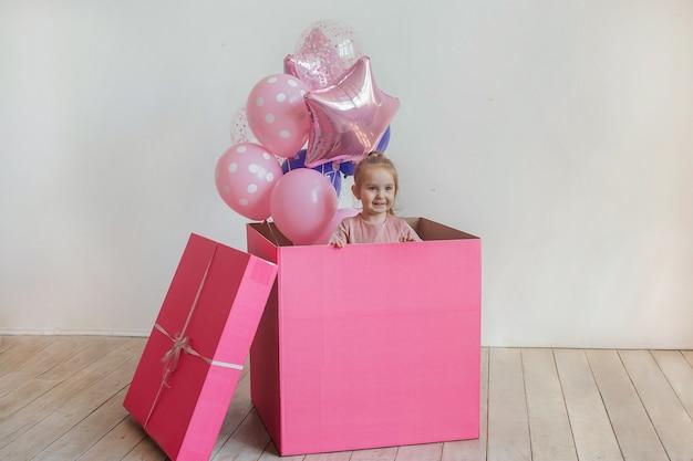 Детский день рождения. маленькая красивая девушка сидит в большой розовой подарочной коробке с воздушными шарами
