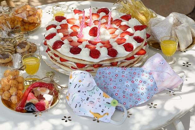 ストロベリーショートケーキと子供のマスクが付いている子供の誕生日のテーブル