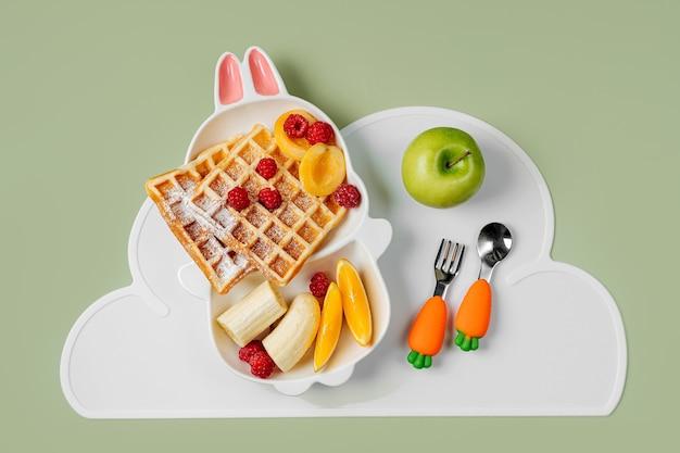 子供の朝食。ワッフルとフルーツのバニーの形をしたかわいいプレート。子供のための食品のアイデア。