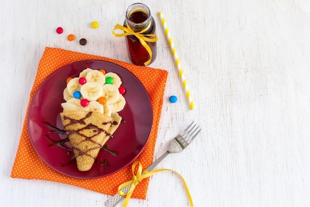Детский завтрак или десерт - блин с бананом, шоколадной начинкой и разноцветными конфетами. приготовление сладкой еды в виде мороженого.