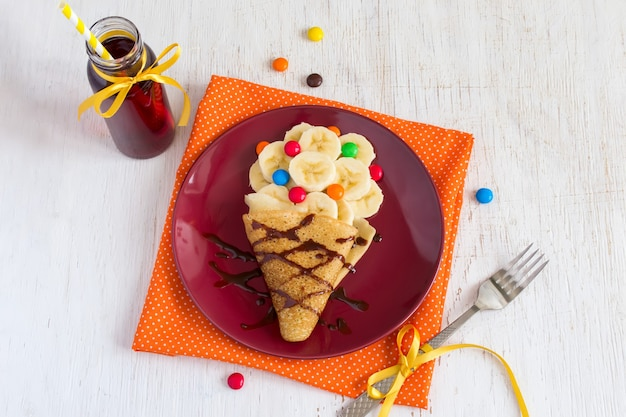 Детский завтрак или десерт - блин с бананом, шоколадной начинкой и разноцветными конфетами. приготовление сладкого блюда в виде мороженого.