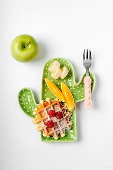 子供の朝食。ワッフルとフルーツが入ったサボテンの形をしたプレート。子供のための食品のアイデア。