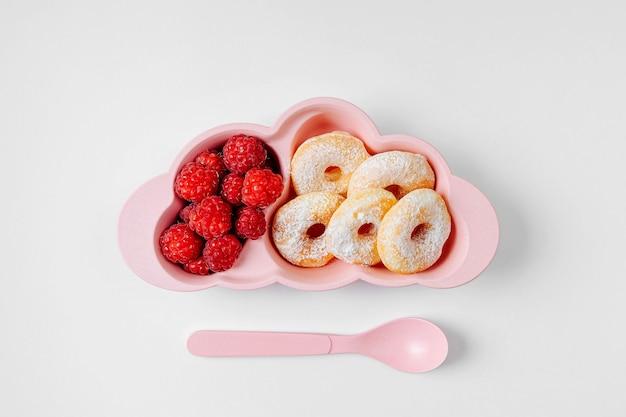 子供の朝食。ドーナツとベリーで雲の形をしたプレート。子供のための食品のアイデア。