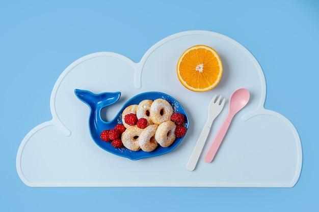 子供の朝食。ドーナツとベリーが入ったクジラの形をしたプレート。子供のための食品のアイデア。
