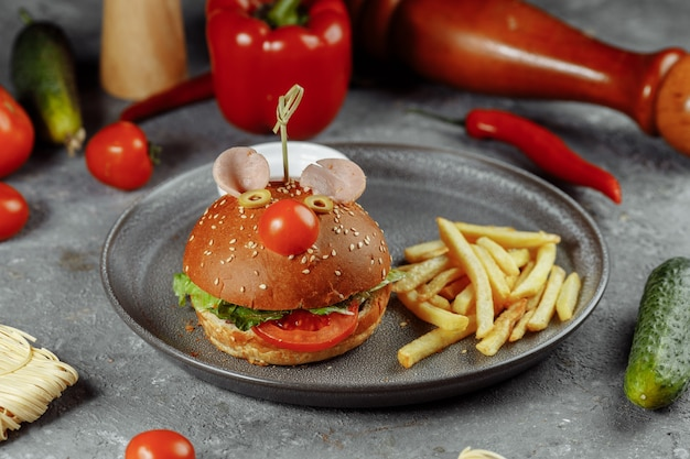 Children's burger in the form of a mouse. burger from the children's menu with fries and sauce.