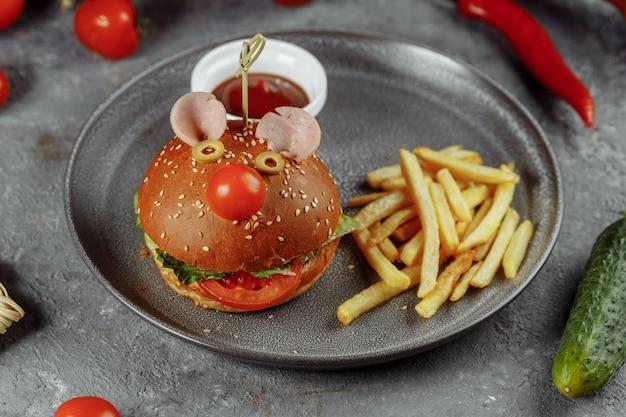 쥐 모양의 어린이 햄버거. 감자튀김과 소스를 곁들인 어린이 메뉴의 버거.