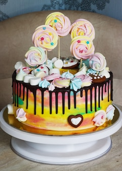 Children's cake rainbow color on a white  with wood meringue