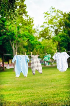 Children's clothes on a rope in the park, expectations of birth concept
