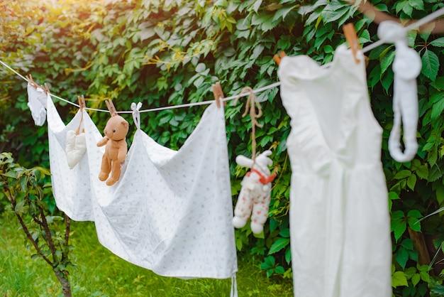 Детская одежда и игрушечный мишка тедди на бельевой веревке сушат после стирки на открытом воздухе.