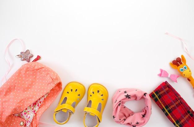 Детская одежда и обувь выложены на белом фоне вид сверху. место для текста.