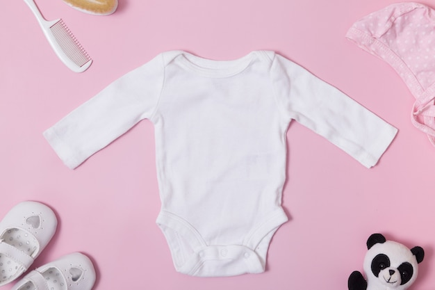 Children's clothing top view, white baby bodysuit mock-up on a pink surface