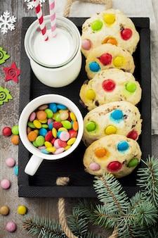Детское печенье с красочными шоколадными конфетами в сахарной глазури на коричневой деревянной поверхности