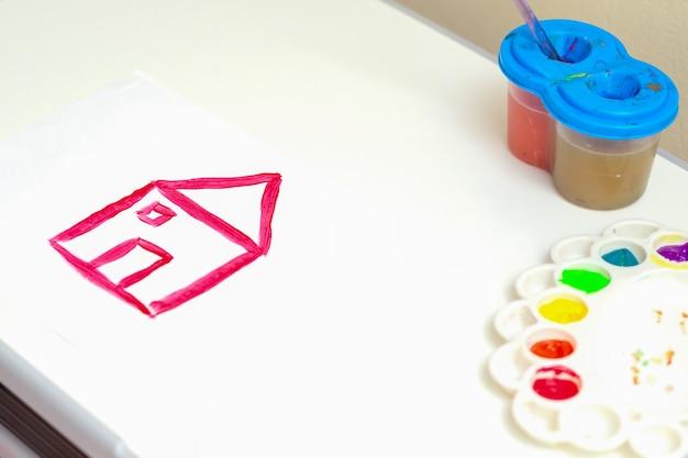 Детское творчество. детский рисунок простого красного дома акварелью на белом листе бумаги.