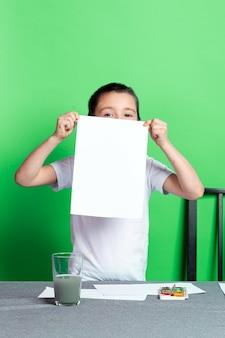 아이들의 창의력. 모형, 소년은 녹색 배경에 그림으로 빈 a4 용지를 보여줍니다.