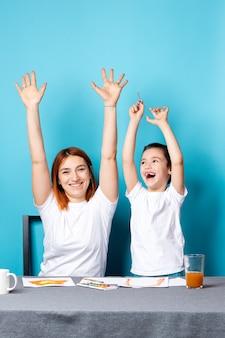 Детское творчество. мама и ребенок сын раскрашивают акварелью домашнее задание для детского сада и радостно поднимают руки вверх на синем фоне