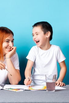 Детское творчество. мама и ребенок сын рисуют акварельную домашнюю работу для детского сада на синем фоне