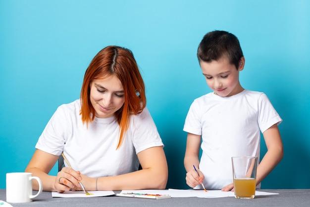 Детское творчество. мать и сын рисуют краской на синем фоне