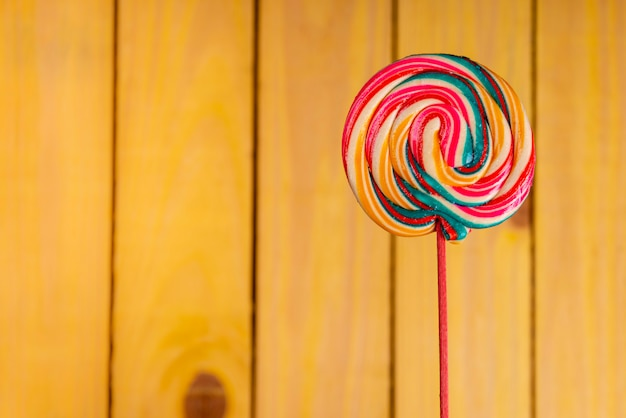 Children's day. colorful lollipop on yellow wood background