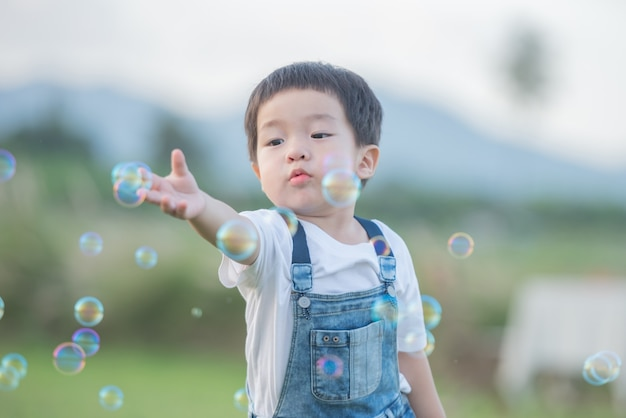 Children's day. little boy blowing soap bubbles in the park. cute toddler boy playing with soap bubbles on summer field. hands up. happy childhood concept. authentic lifestyle image.