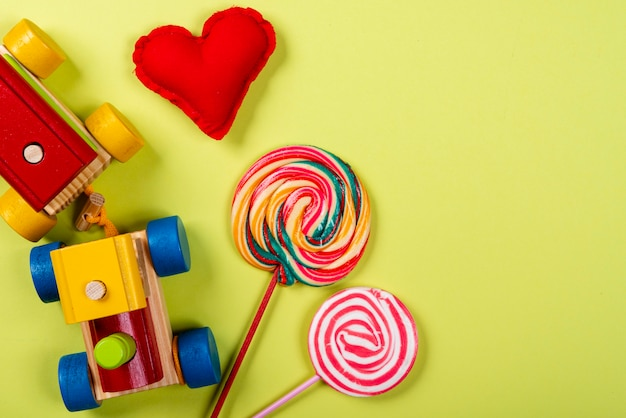 Children's day. wooden train, lollipop and heart made of fabric on neon green background