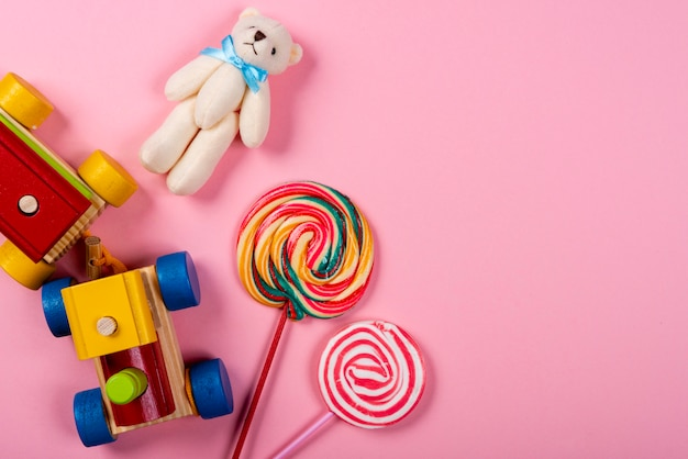 Children's day. wooden train, lollipop and teddy bear over pink background