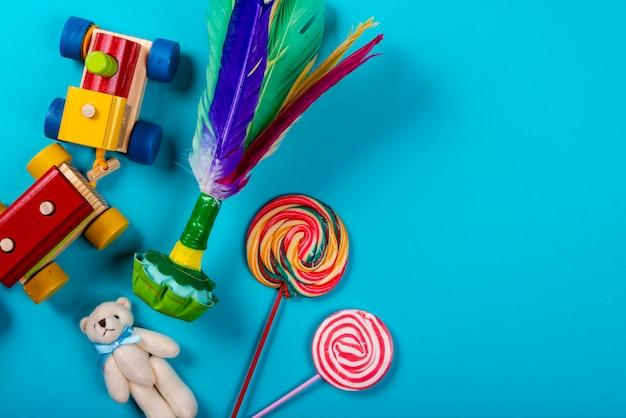 Children's day. wooden train, shuttlecock, teddy bear, lollipops on neon blue background