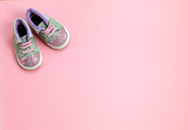 Children's denim sports shoes for girls, stands on a pink background.