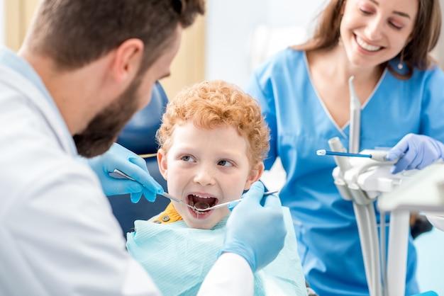 オフィスの歯科用椅子に座っている少年の赤ちゃんの歯を調べる子供の歯科医と助手