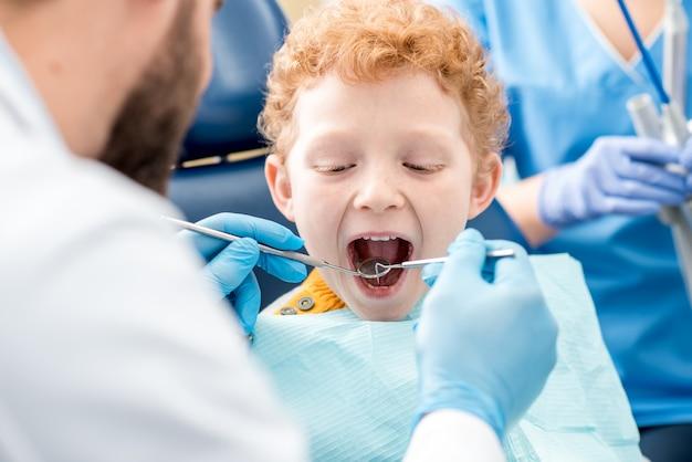 オフィスの歯科用椅子に座っている少年の赤ちゃんの歯を調べる子供の歯科医