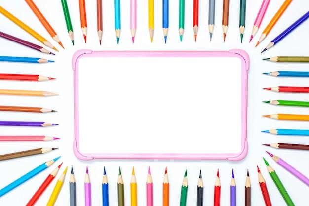 Детский цифровой планшет на белом столе с рамкой цветных карандашей для рисования