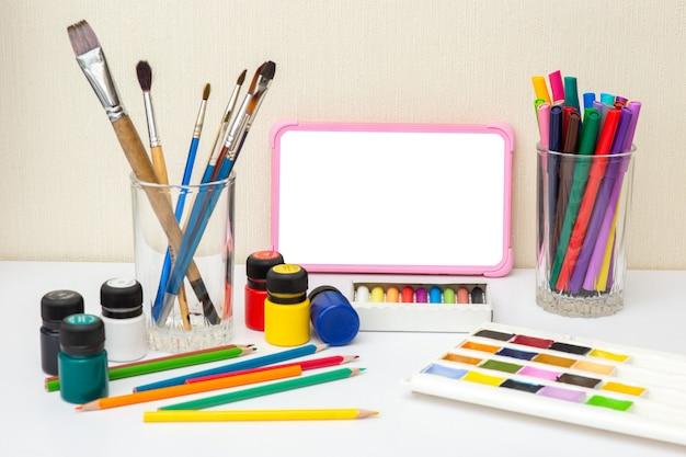 Детский цифровой планшет с пустым экраном на белом столе с разноцветными принадлежностями для рисования.