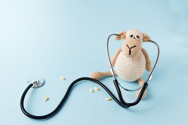 Children's doctor concept. sheep toy and stethoscope on blue background