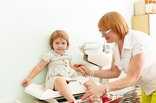 Детский доктор, взвешивающий ребенка