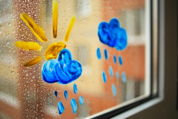Children's drawing of clouds and sun in colors on a wet window