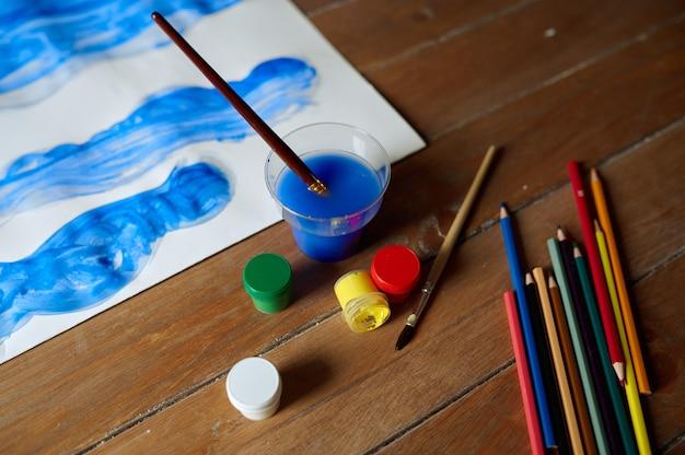 子供の絵、木製のテーブルの絵の具と鉛筆、ワークショップのコンセプト、誰も。美術学校でのレッスン。若い画家の作品、楽しい趣味、幸せな子供時代。クリエイティブな開発
