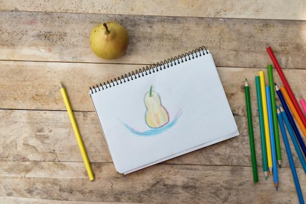 Детский рисунок, груша и цветные карандаши. деревянный стол. вид сверху
