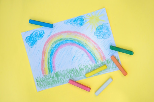 Детский рисунок с красочной радугой на листе бумаги