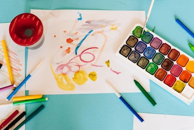 Детские рисунки, цветные карандаши и маркеры и краски вид сверху